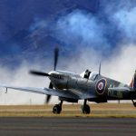 Supermarine Spitfire takes off runway with mountains in the background