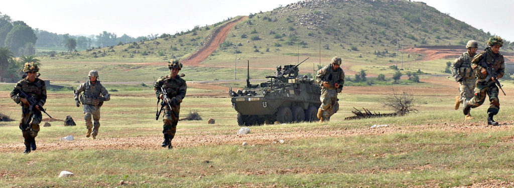 "CAMP BUNDELA, India (Oct. 15, 2009) – Indian Army Soldiers assigned to the 94th Armored Brigade along with U.S. Army Soldiers assigned to Troop C, 2nd Squadron, 14th Cavalry Regiment ""Strykehorse,"" 2nd Stryker Brigade Combat Team, 25th Infantry Division, from Schofield Barracks, Hawaii charge the uphill range during Exercise Yudh Abhyas 09, Oct. 15. YA09 is a bilateral exercise involving the Armies of India and the United States."