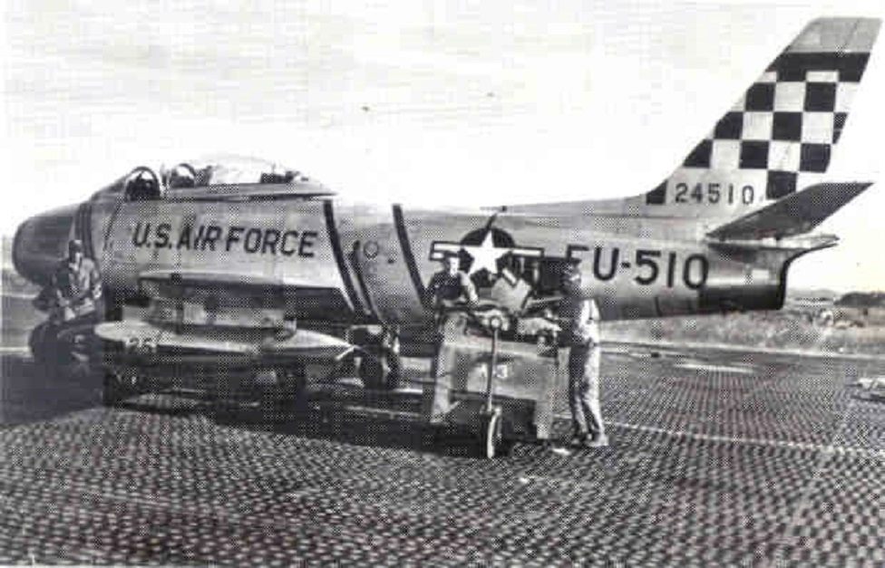 """Ground crews prepare an F-86 Sabre with its 51st Fighter Interceptor Wing """"Checkertail"""" for flight during the Korean War."""