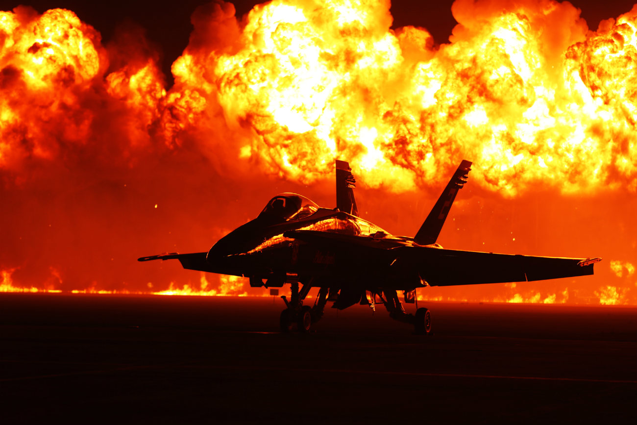 US Military Aircraft at Night Images - FA-18 Hornet with flames in the background