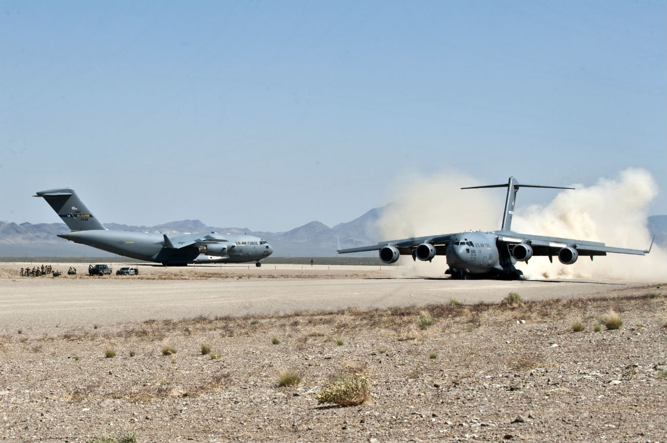 2 C-17 Globemaster IIIs prepare to take off from a dirt runway