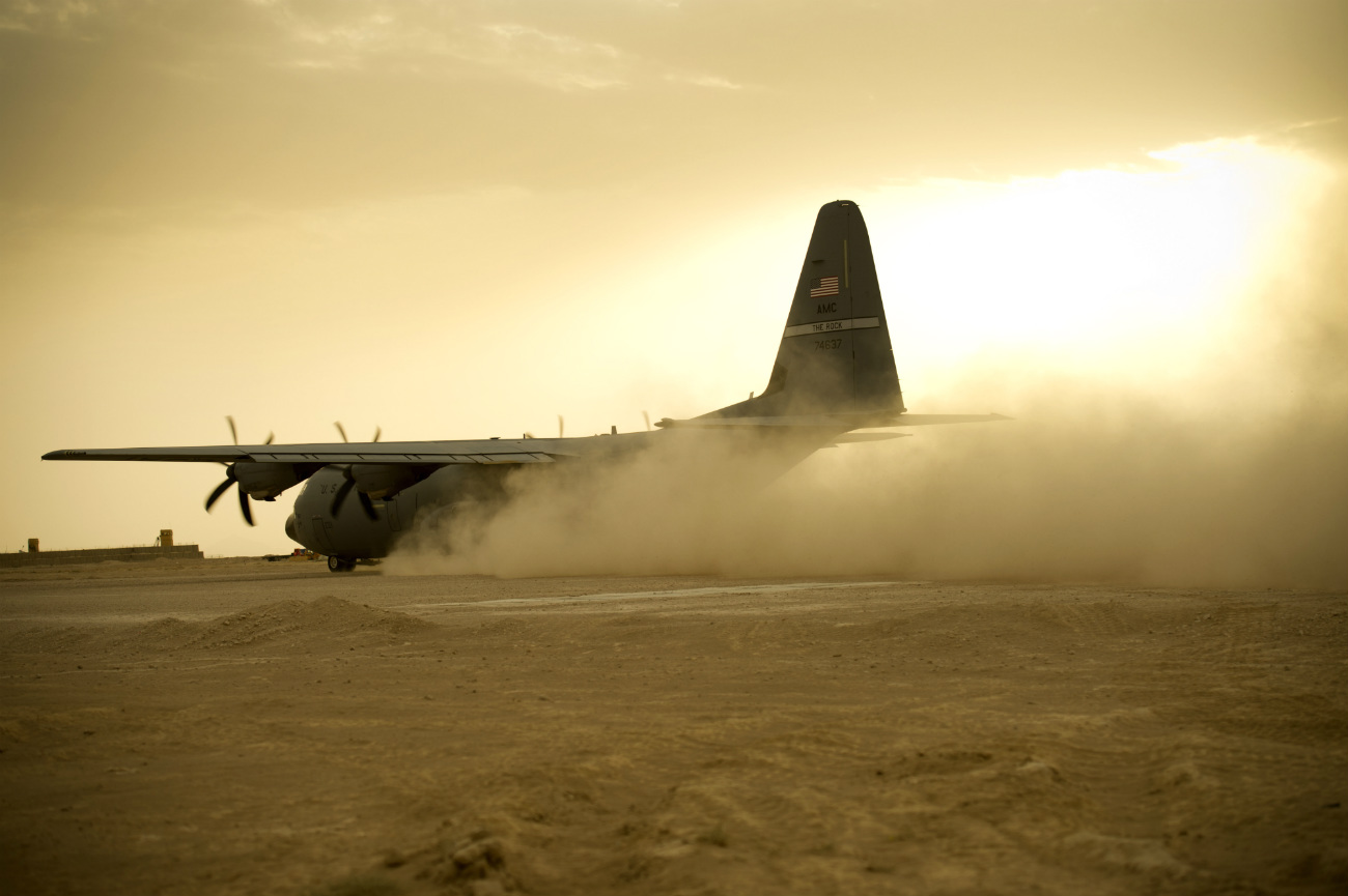 C-130 takes off on a dirt landing strip