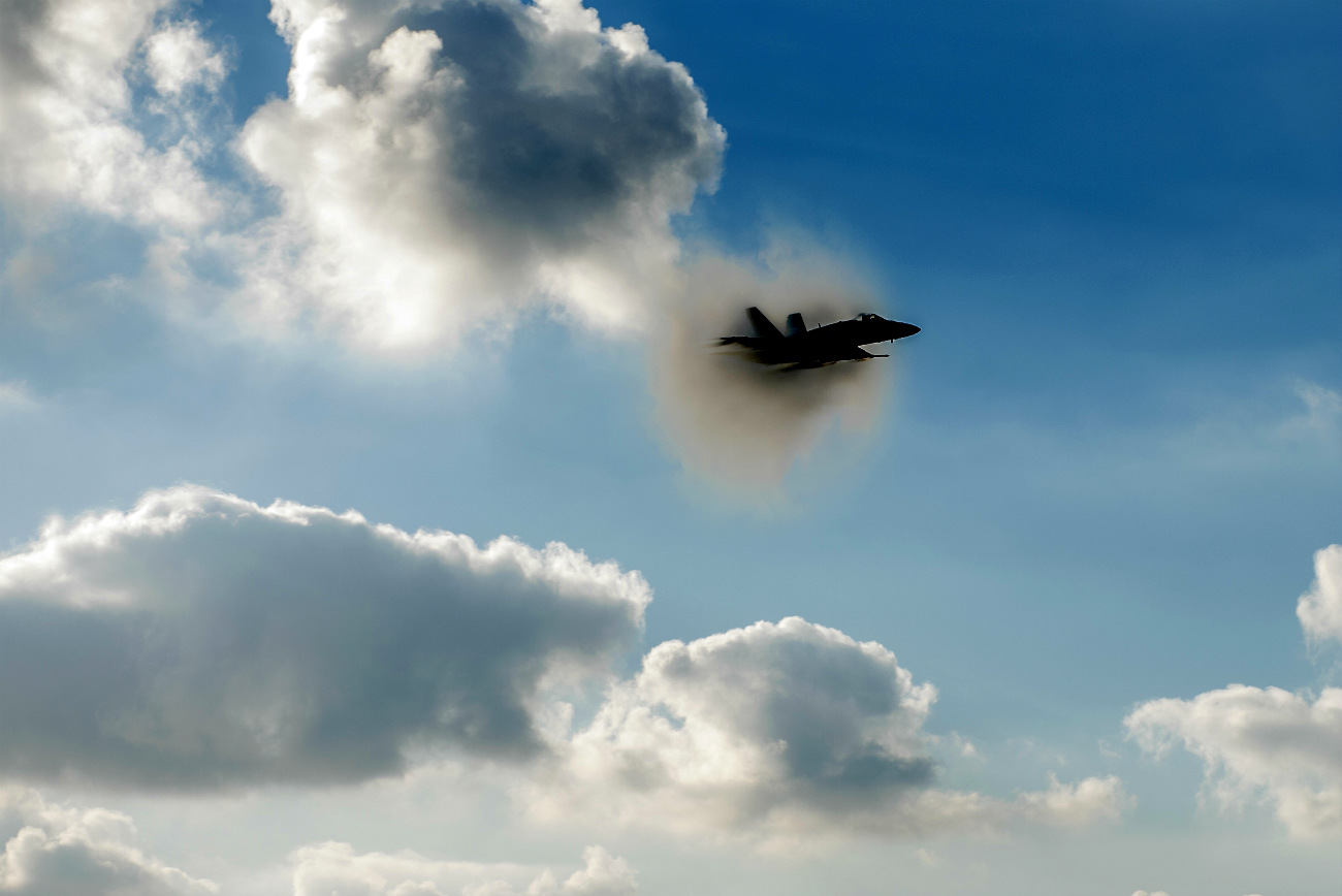 FA-18C Hornet breaks the sound barrier above the flight deck of aircraft carrier