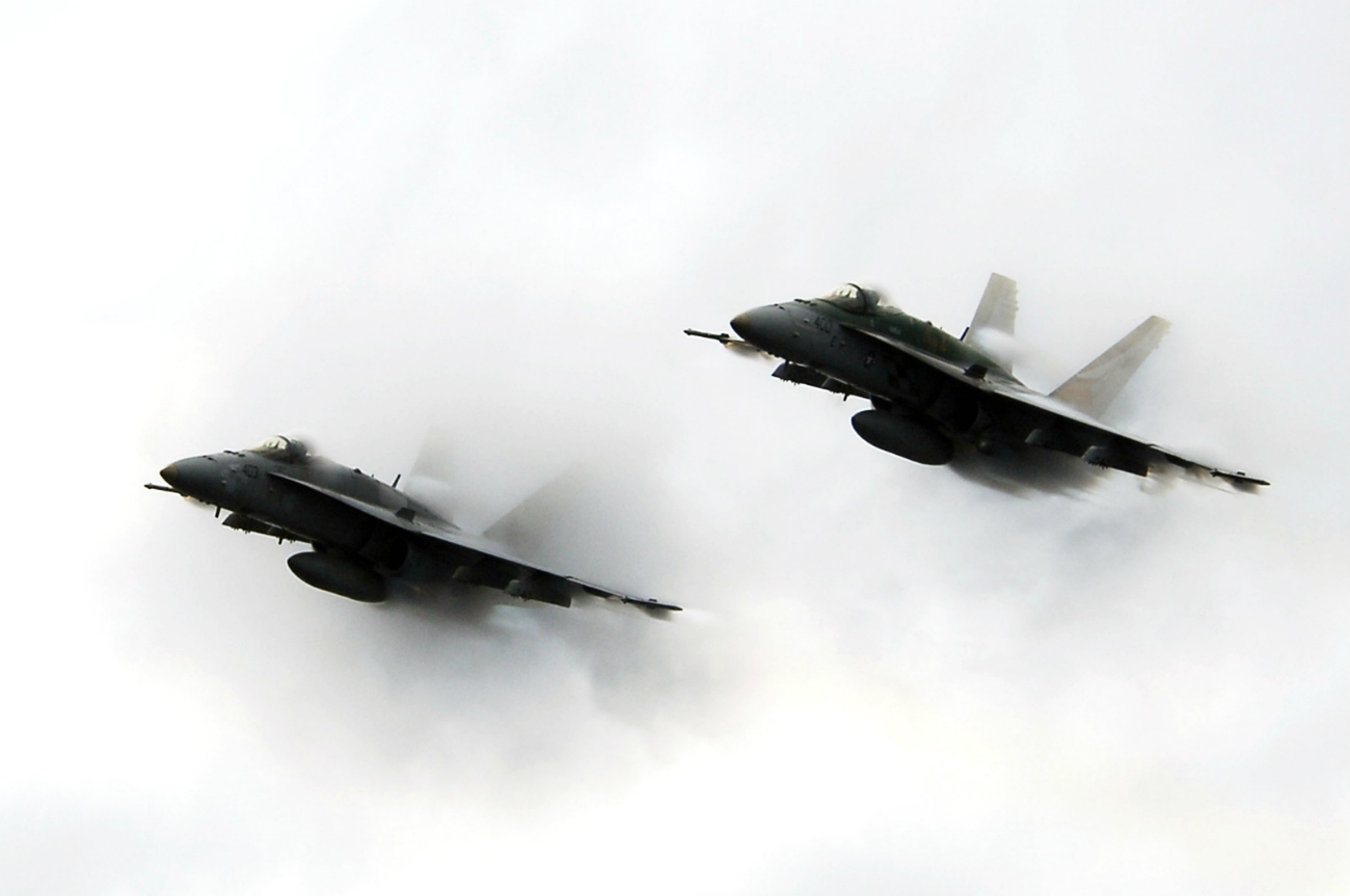 Two FA-18C Hornets punch through a cloud of water vapor while breaking the sound barrier