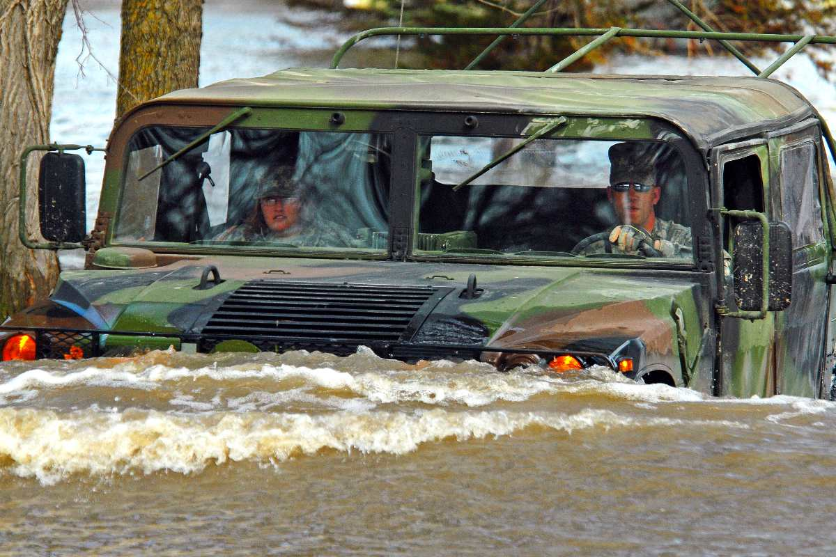 U.S. Army Staff Sgt. William Griffin, with the 136th Combat Sustainment Support Battalion, drives a Humvee on a flooded road in Fort Ransom, N.D., April 15, 2009. Griffin and Spc. Jessica Sandberg, with the 132nd Quartermaster Battalion, are making a welfare visit to a rural civilian whose home is surrounded by water.