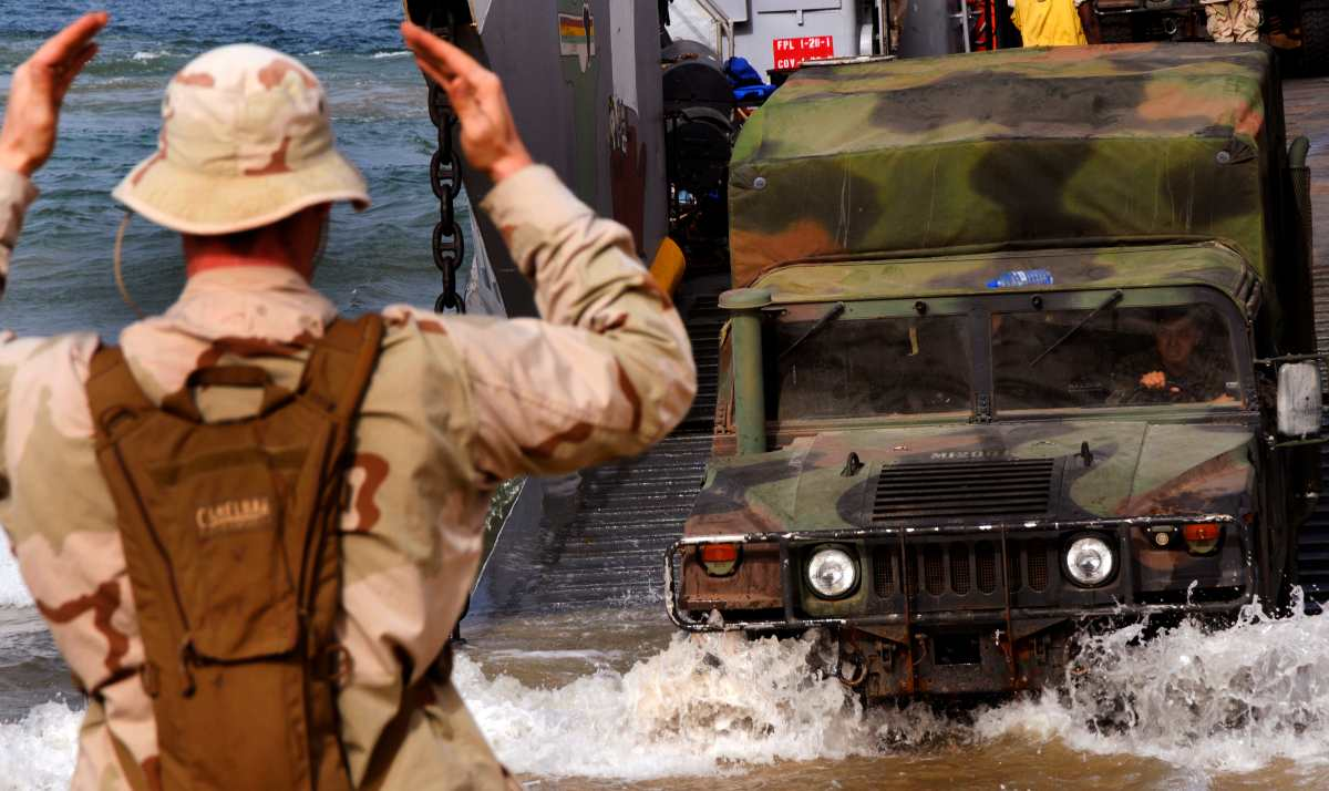 a Humvee as it disembarks from Landing Craft Unit 1660, assigned to Assault Craft Unit 2, during an offload of U.S, Spanish, Portuguese and British Marines from the embarked Security Cooperation Marine Air-Ground Task Force and Seabees assigned to Naval Mobile Construction Battalion 7.